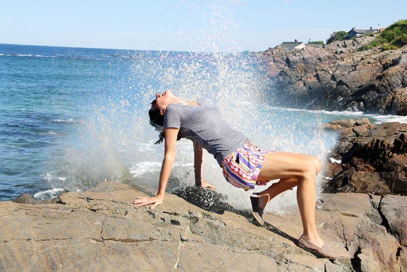 Femme sur une roche avec une vague se brisant là-dessus photos libres de droits