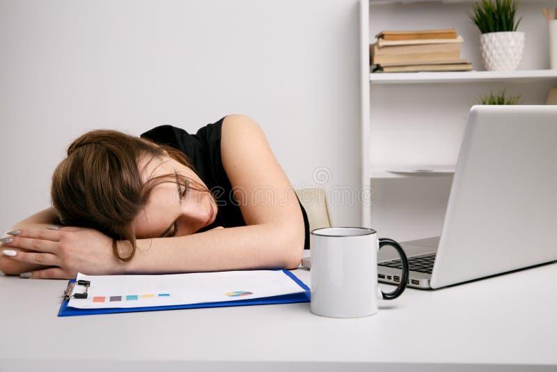 Femme surchargée dans le bureau dormant à son bureau de travail photos libres de droits