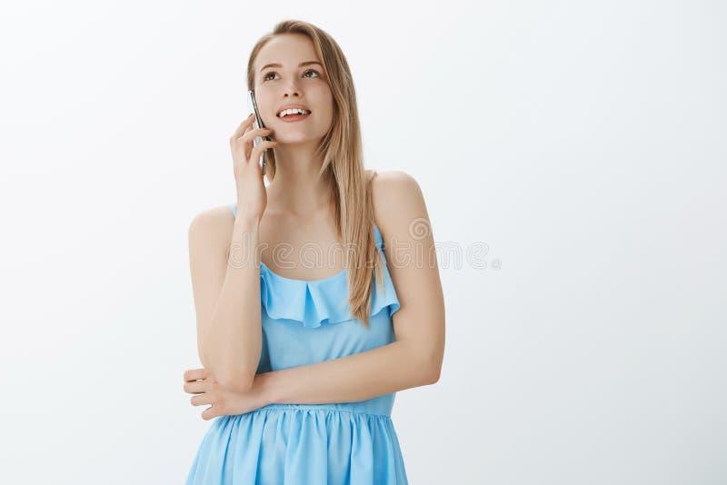 Femme talktative et sortante belle d'ami avec les cheveux blonds dans la robe bleue parlant à l'ami par l'intermédiaire d'augment photos stock