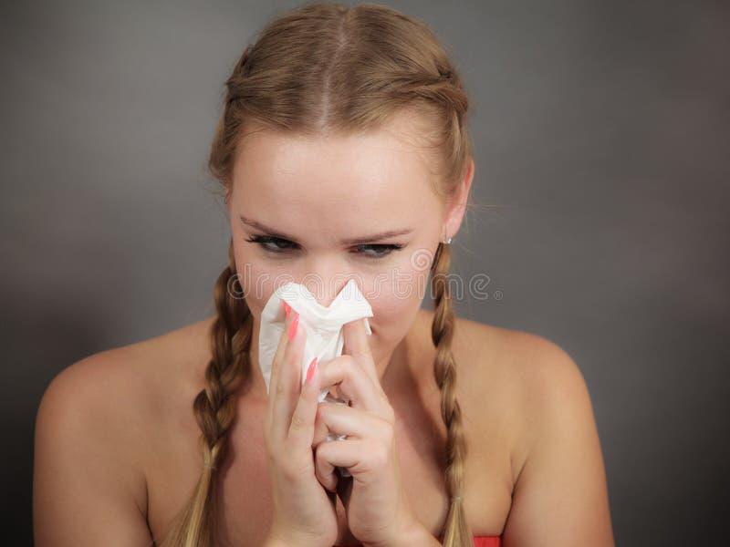 Femme ?tant malade ayant l'?ternuement de grippe dans le tissu photographie stock