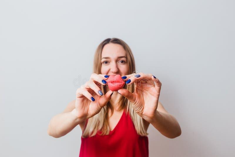 Femme tenant de grandes lèvres d'un silicone sur le fond blanc image libre de droits