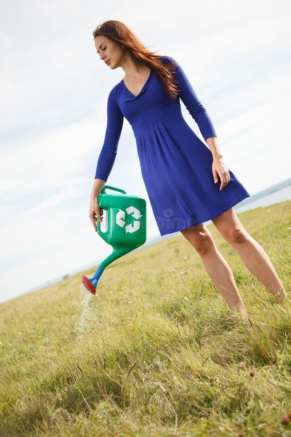 Femme tenant dehors le pot d'arrosage vert avec réutiliser le signe photo stock