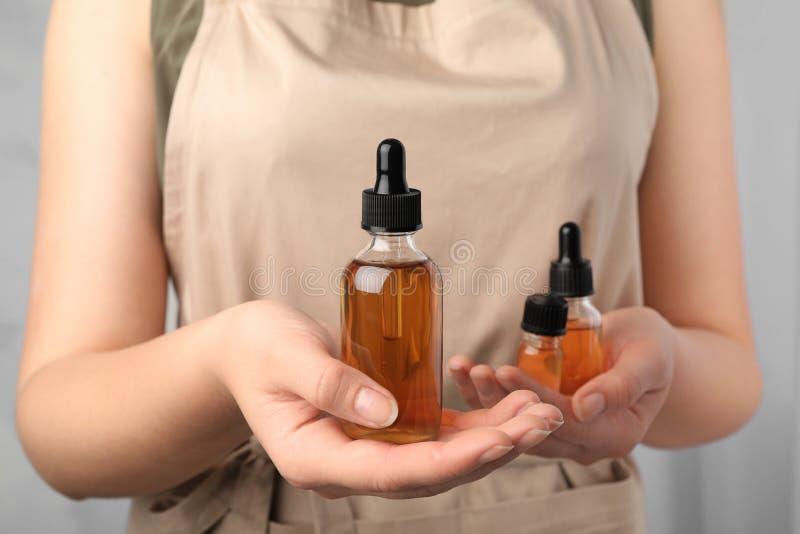 Femme tenant des bouteilles d'huiles essentielles image libre de droits