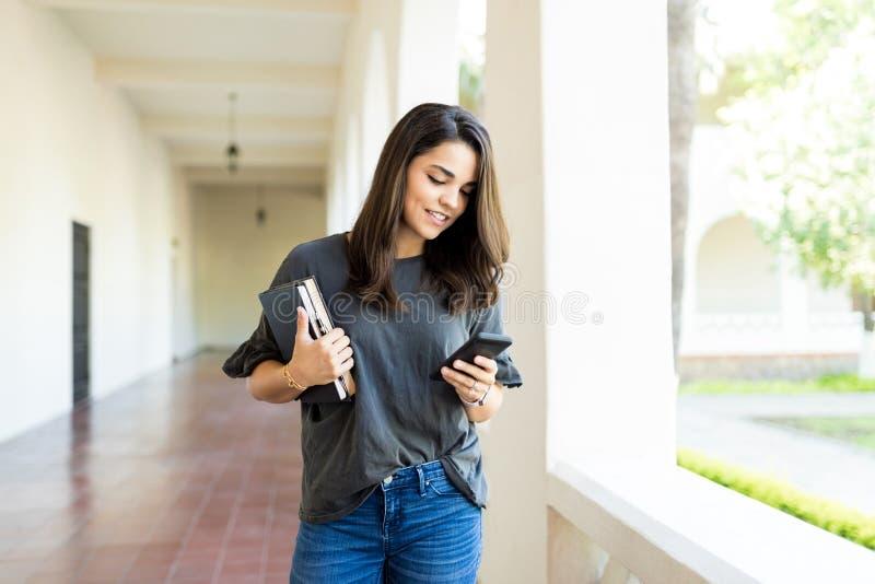 Femme tenant des livres tout en vérifiant le site social sur Smartphone images stock