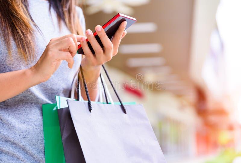 Femme tenant des paniers faisant des achats en ligne sur son mobile images libres de droits
