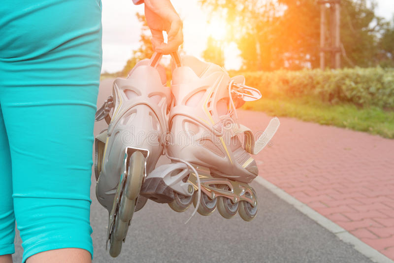 Femme tenant des patins de rouleau image stock