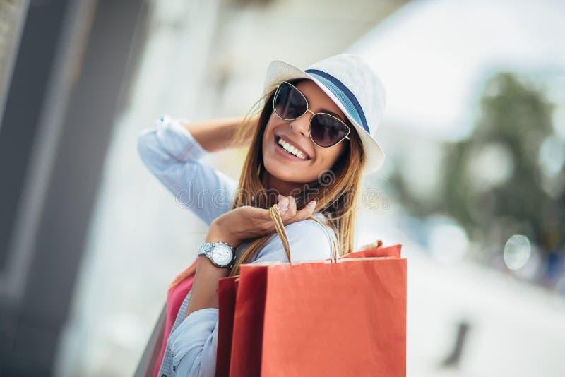 Femme tenant des sacs à provisions et souriant - dehors images stock