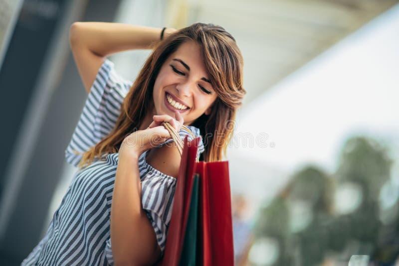 Femme tenant des sacs ? provisions et souriant - dehors image stock