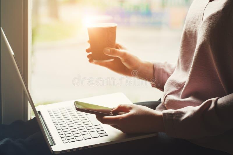 Femme tenant et à l'aide du smartphone et l'écran tactile, le café potable et travailler sur l'ordinateur portable photos stock