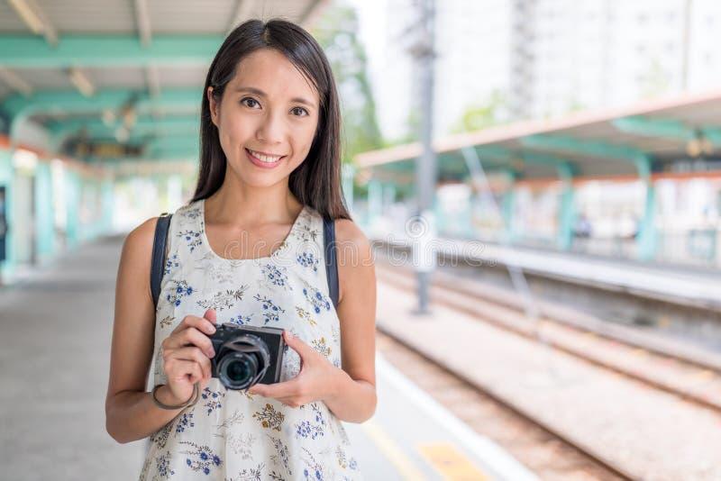 Femme tenant l'appareil-photo dans la gare légère de Hong Kong photographie stock libre de droits