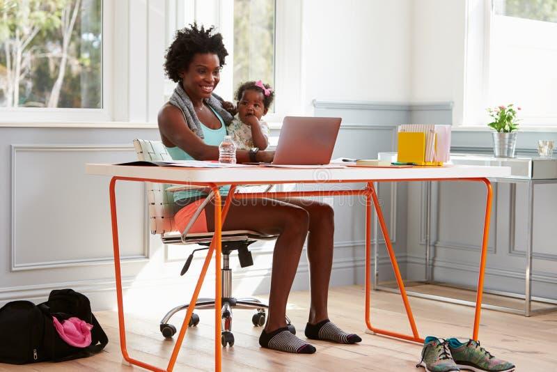 Femme tenant l'enfant à l'aide de l'ordinateur à la maison après l'exercice photo stock
