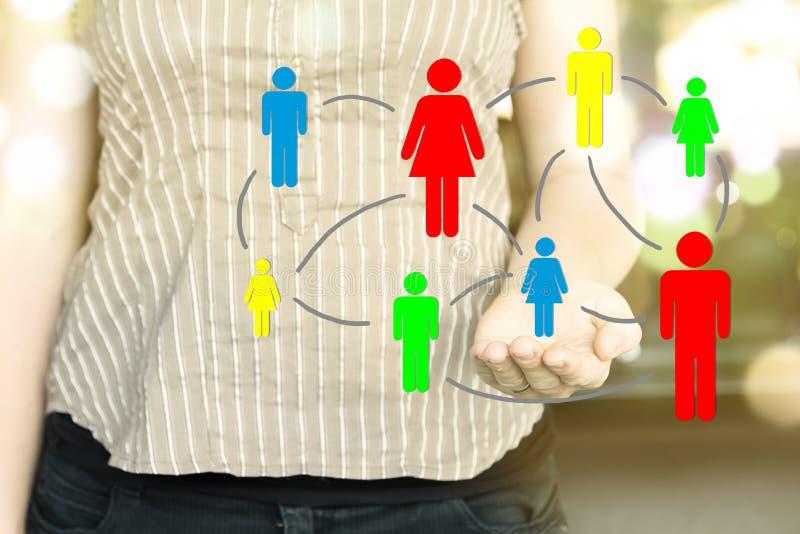 Femme tenant l'illustration des icônes colorées de personnes reliées entre eux Concept social de medias photo libre de droits