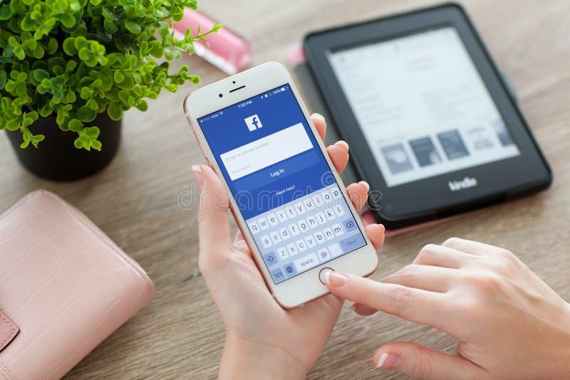 Femme tenant l'iPhone 6S Rose Gold avec Facebook sur l'écran photographie stock
