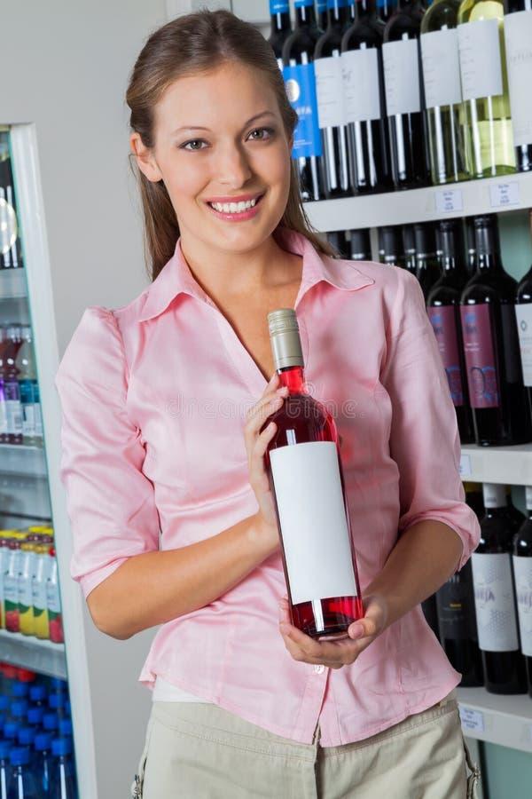 Femme tenant la bouteille d'alcool au supermarché image stock
