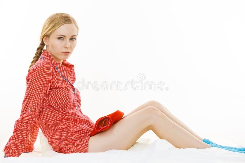 Femme tenant la bouteille d'eau d'un rouge ardent chaude photographie stock