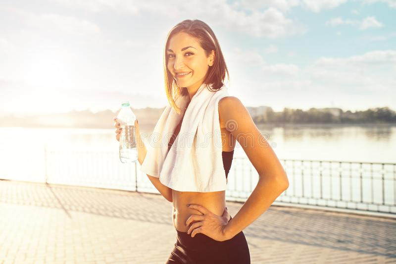 Femme tenant la bouteille de l'eau et d'une serviette images stock