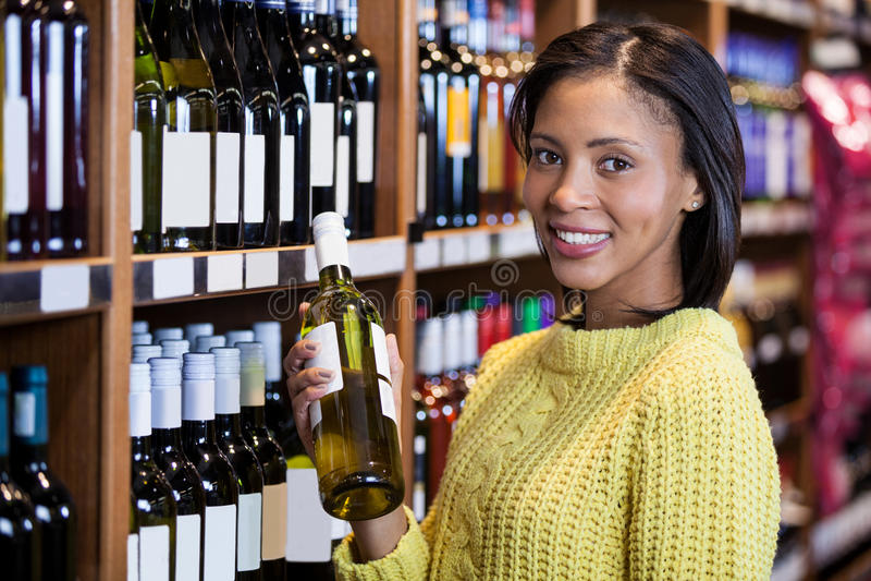 Femme tenant la bouteille de vin dans la section d'épicerie photographie stock libre de droits