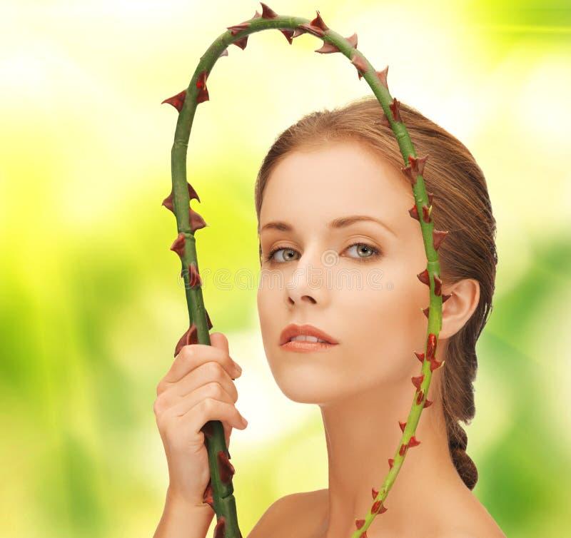 Femme tenant la branche avec des épines photographie stock