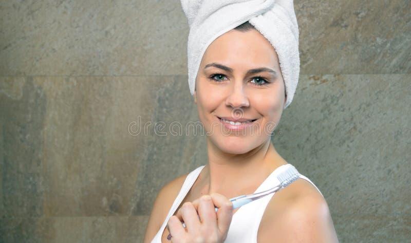 Femme tenant la brosse à dents devant son blanc image stock