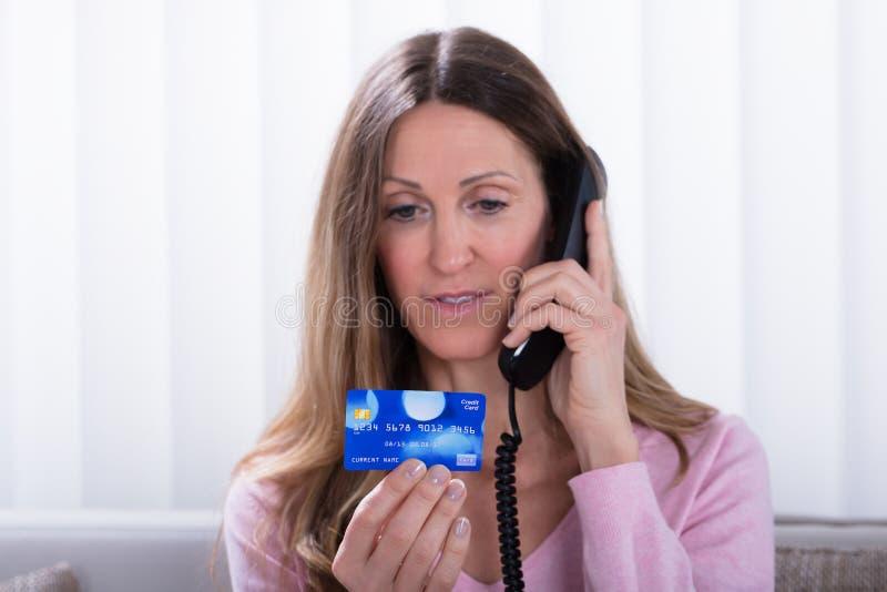 Femme tenant la carte de crédit tout en parlant au téléphone photos libres de droits