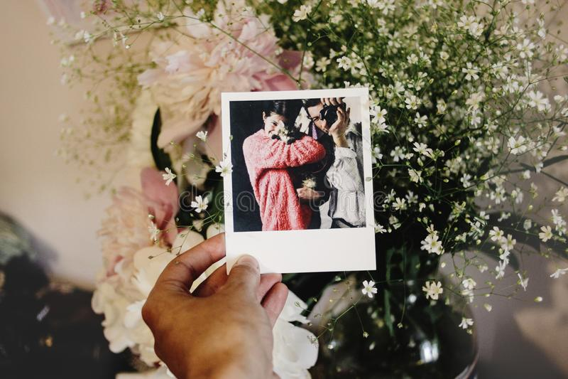 Femme tenant la carte de photo avec la photo polaroïd de sa famille dessus images libres de droits