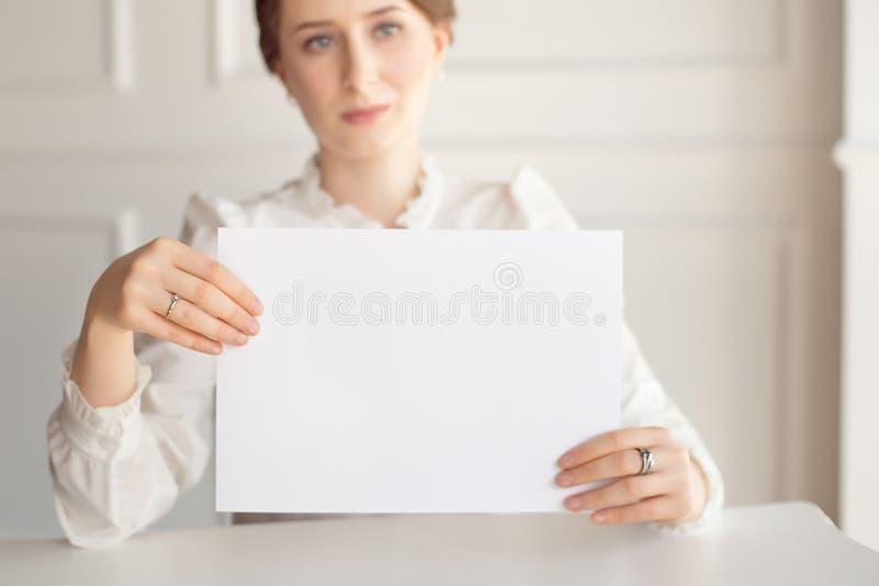 Femme tenant la carte de visite professionnelle de visite blanche sur le fond blanc de mur photo libre de droits