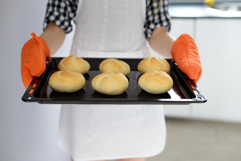 Femme tenant la casserole chaude de torréfaction avec les petits pains de pain chauds et fraîchement cuits au four images stock