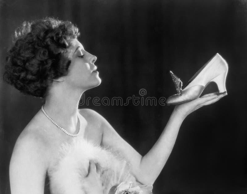Femme tenant la chaussure (toutes les personnes représentées ne sont pas plus long vivantes et aucun domaine n'existe Garanties d photos libres de droits