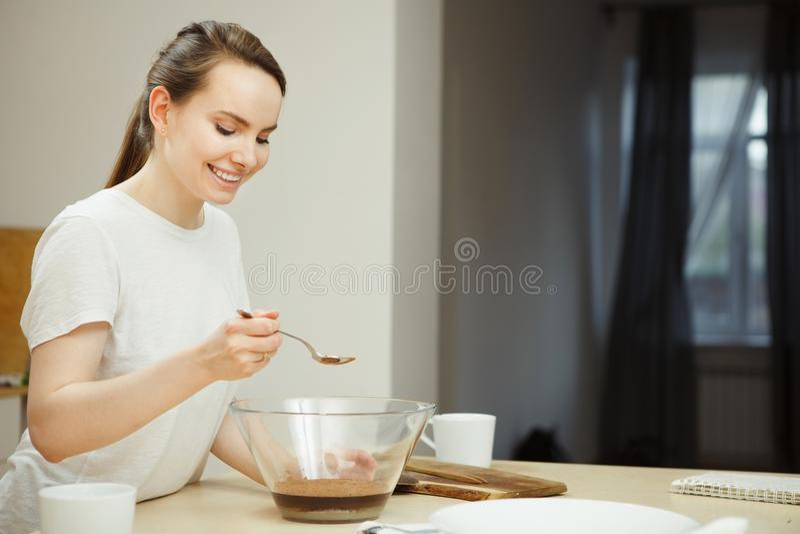 Femme tenant la cuillère au-dessus du bol en verre, préparation de dessert doux photos stock