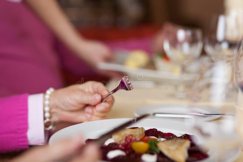Femme tenant la fourchette et le couteau avec le plat sur le Tableau de restaurant images libres de droits