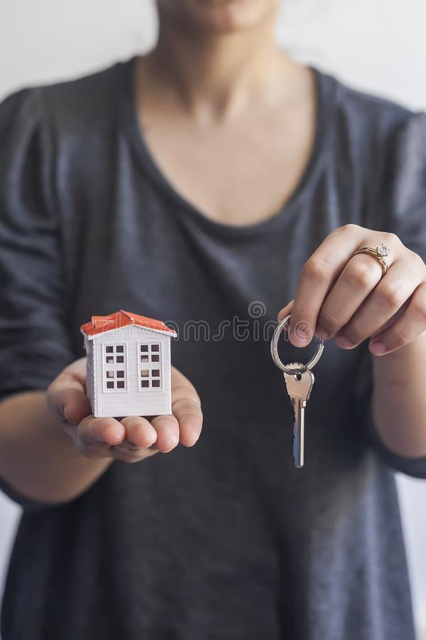 Femme tenant la maison miniature et les clés de jouet Vrai agent immobilier tenant les clés et la maison de jouet Achetant ou ven photos libres de droits