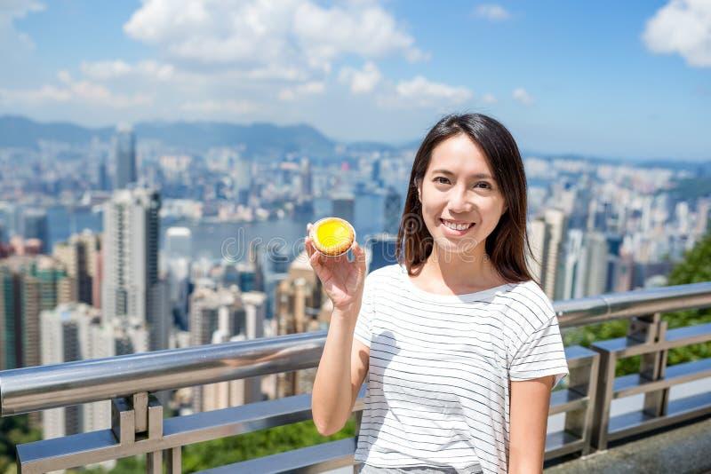 Femme tenant la nourriture célèbre de Hong Kong de la tarte d'oeufs photo stock