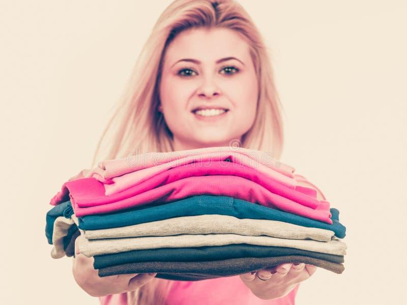 Femme tenant la pile des vêtements pliés image libre de droits