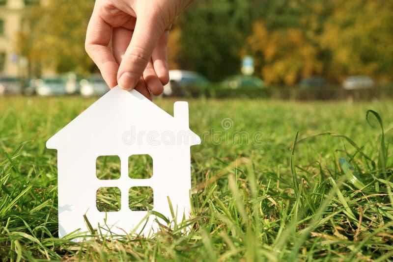 Femme tenant la silhouette de papier de la maison dans l'herbe dehors, l'espace pour le texte photographie stock