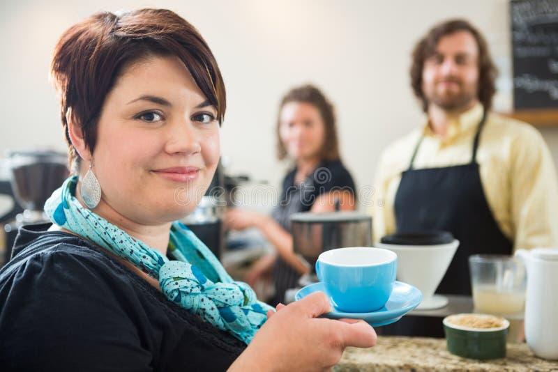 Femme tenant la tasse de café avec des propriétaires en café photos libres de droits