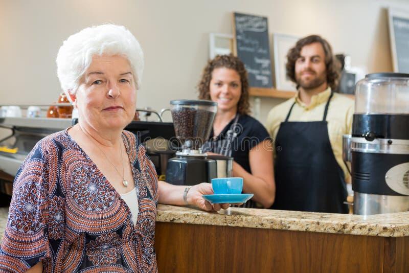 Femme tenant la tasse de café avec des travailleurs au compteur images stock