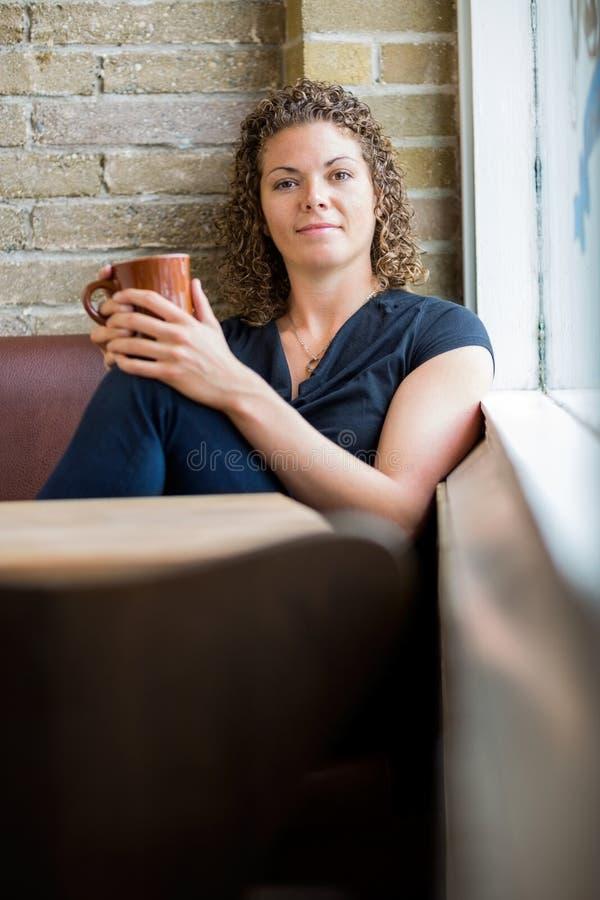 Femme tenant la tasse de café dans le cafétéria photographie stock libre de droits