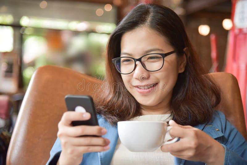 Femme tenant la tasse de café et à l'aide du téléphone intelligent image libre de droits