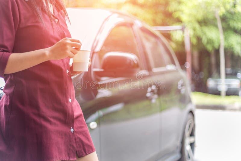 Femme tenant la tasse de café jetable près de voiture photographie stock