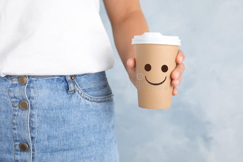 Femme tenant la tasse de café de papier avec le sourire sur le fond de couleur image libre de droits