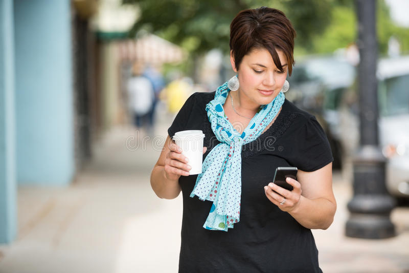 Femme tenant la tasse de café tandis que transmission de messages  photographie stock
