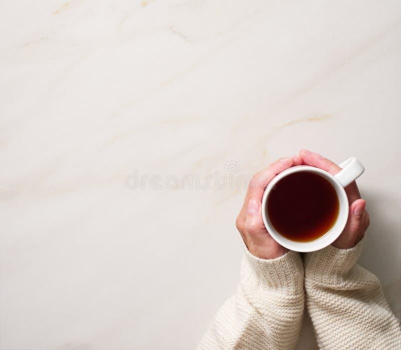 Femme tenant la tasse de thé chaud sur la table beige en pierre, mains dans le chandail chaud avec la tasse, concept de matin d'h photo stock