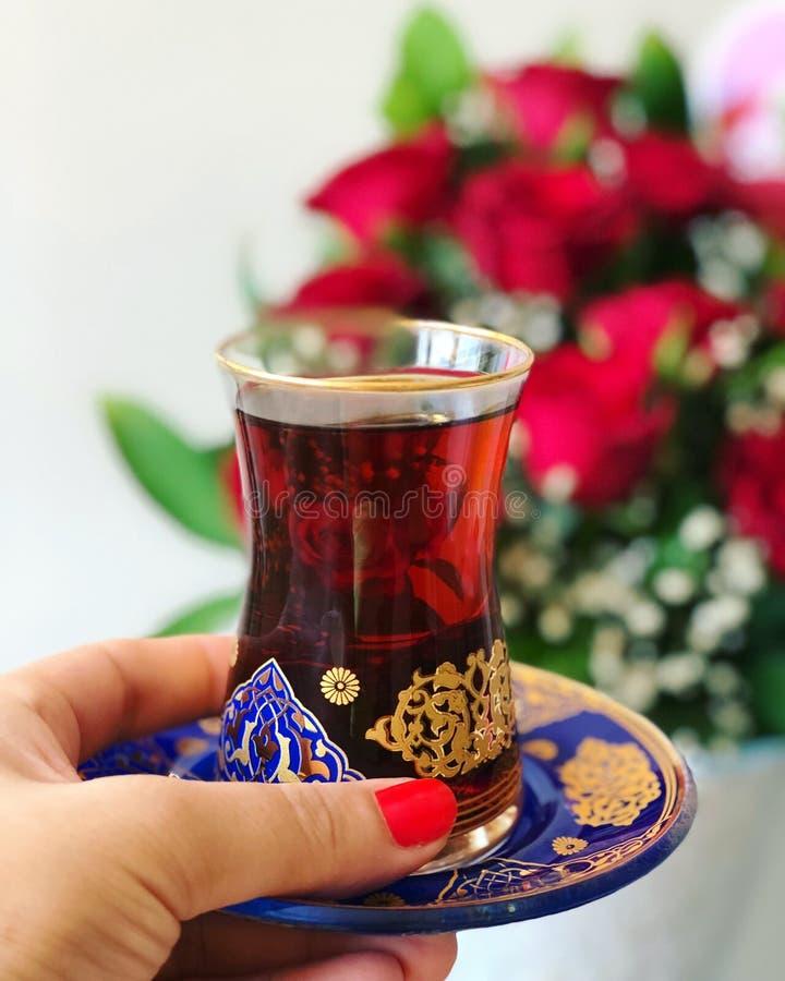 Femme tenant la tasse de thé turc traditionnel, fond de roses rouges photo stock