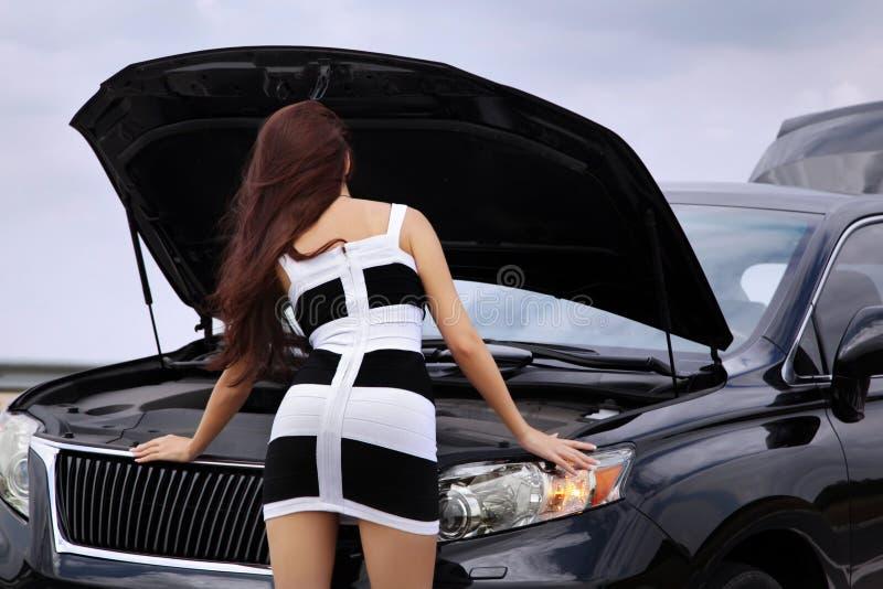 Femme tenant la voiture proche avec un capot ouvert photo libre de droits