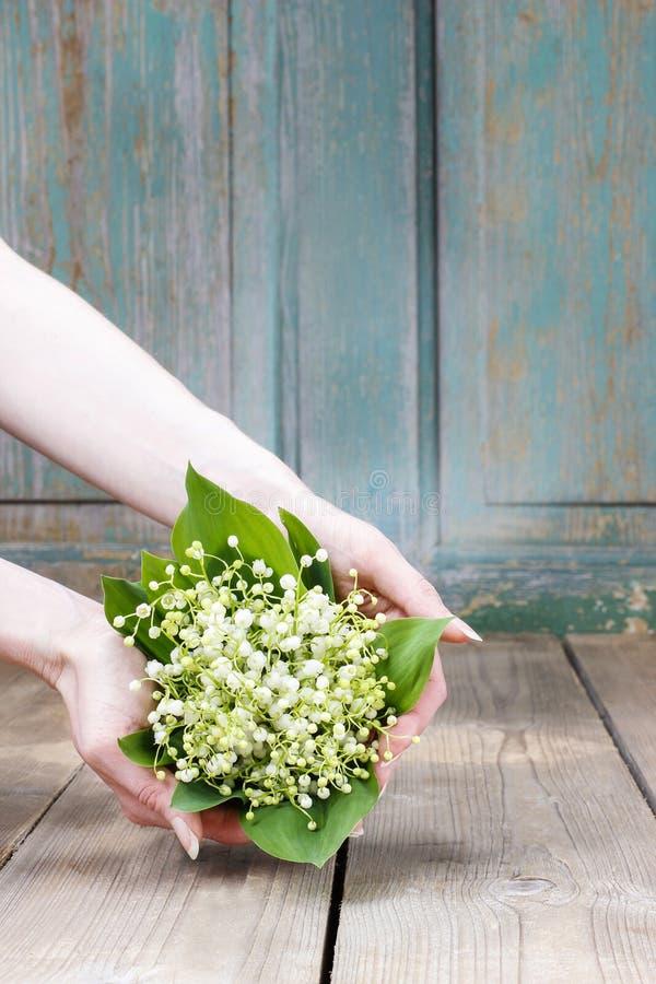 Femme tenant le bouquet des fleurs du muguet photographie stock libre de droits