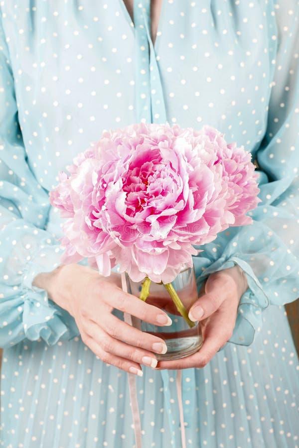Femme tenant le bouquet des pivoines roses images stock