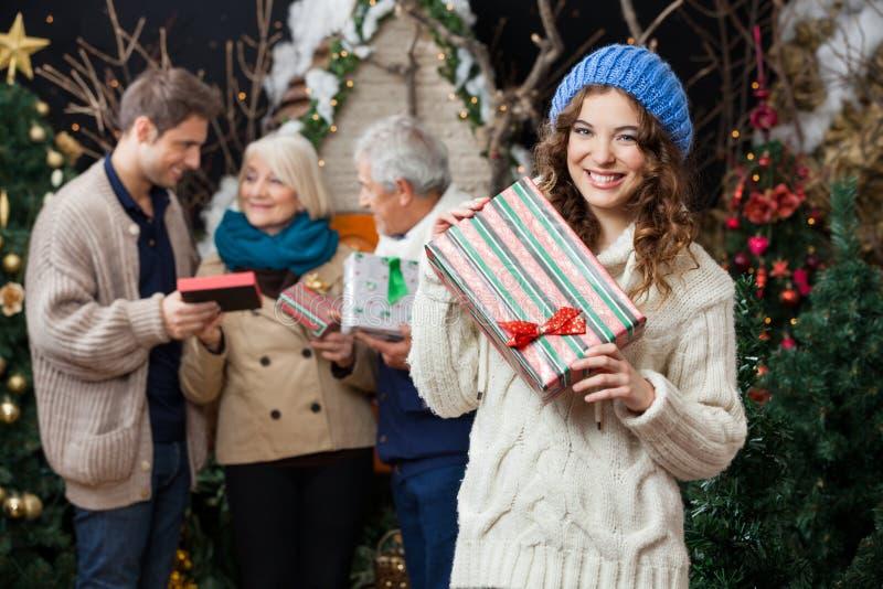 Femme tenant le cadeau de Noël avec la famille dedans photo stock