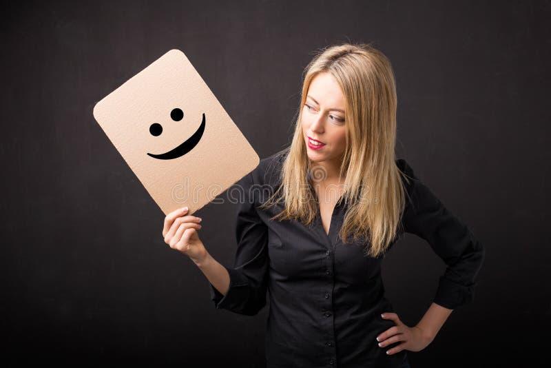 Femme tenant le carton avec le smiley photos stock