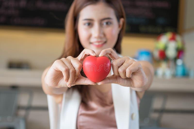 Femme tenant le coeur rouge dans des mains photo stock