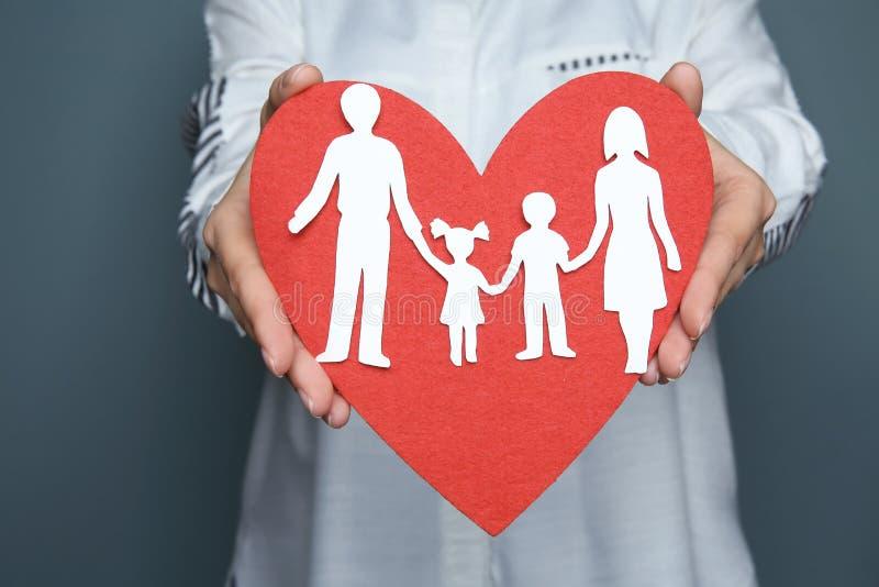 Femme tenant le coupe-circuit rouge de coeur et de famille de papier, photo stock